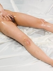 Oily beauty Karina Oshima teasing her juicy little pussy on a big white bed